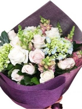 Pink and white rose bouquet accented with assorted greenery