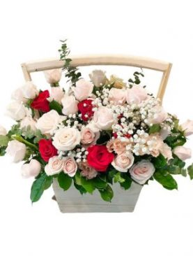 Pink, white, and red  roses in a wooden basket accented with assorted greenery