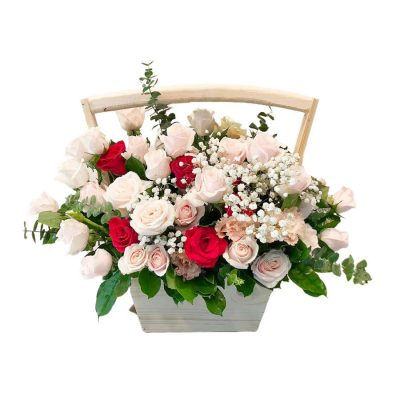 A wooden basket of pink roses accented with assorted greenery