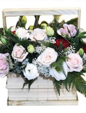 Pink, white and red roses in wooden basket