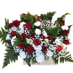 A wooden basket of two dozen assorted roses