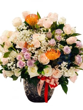 Two dozen of assorted roses in a vase